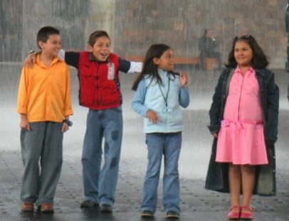 Mexican kids playing in the rain. Great example of Hispanic culture.